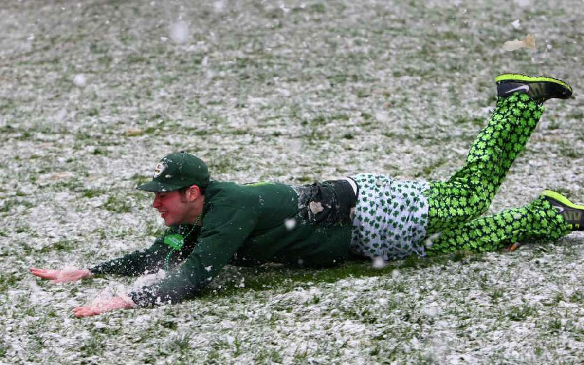 Dan Balmer of Bellingham dives into the snow during a soggy St. Patrick's Day Dash on Saturday, March 17, 2012 in downtown Seattle. Thousands of people participated in the annual event. By the end of the race large snowflakes were falling on participants.