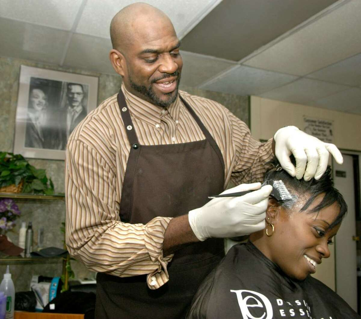 Anthony and Tanisha Jamison, both stylists, are owners of AT & J's Beauty Salon on Division St. which is part of the Wooster Village area. On Wednesday, during a down time, Anthony did his wife's hair.