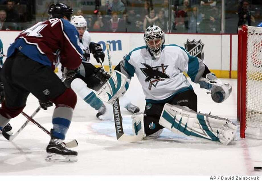 San Jose Sharks goalie Vesa Toskala, right, of Finland makes a pad save on a shot off the stick of Colorado Avalanche's Antti Laaksonen of Finland in the first period of an NHL hockey game in Denver on Wednesday, April 5, 2006. (AP Photo/David Zalubowski) Photo: DAVID ZALUBOWSKI