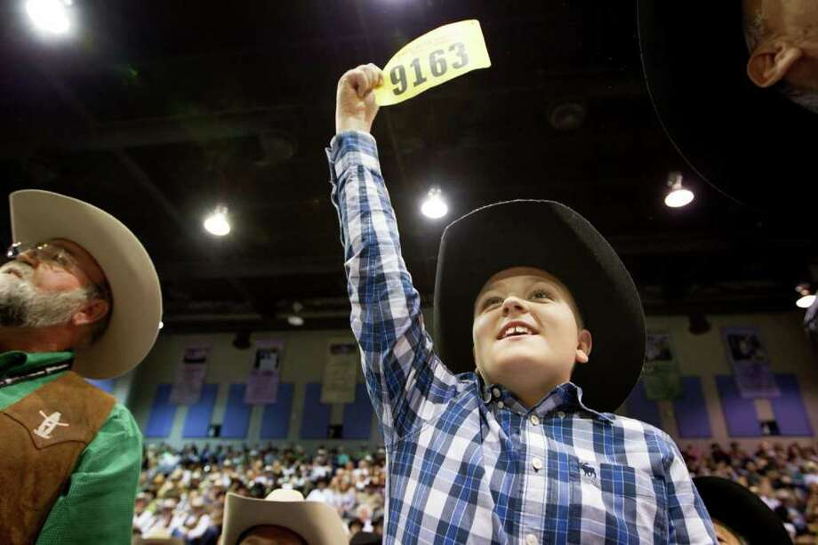 Kyle Bruegger raises his number on behalf of the group of of E.D. Lester, left, along with Chris Bruegger, Rico Flores and Roger Bethune as they make their winning bid for the Reserve Grand Champion during the Junior Market Steer Auction at the Houston Livestock Show and Rodeo=.  The reserve Grand Champion, owned by Emily Kelley of Yoakum, sold for  $250,000, highest amount since 2005. Photo: Smiley N. Pool, Houston Chronicle / © 2012  Houston Chronicle