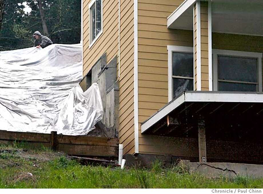 A construction worker adjusts a tarp at a home under construction on Larchmont Drive that was red-tagged by officials after several significant cracks were found (lower right) in the foundation on 4/4/06 in unincorporated Broadmoor Village, CA.  PAUL CHINN/The Chronicle MANDATORY CREDIT FOR PHOTOG AND S.F. CHRONICLE/ - MAGS OUT Photo: PAUL CHINN