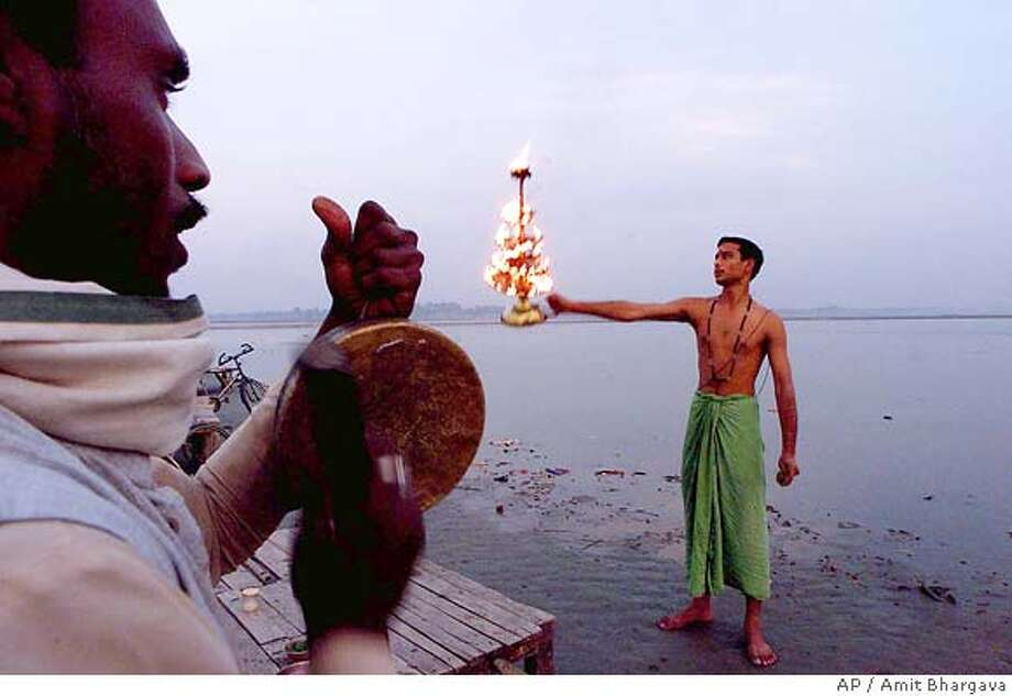 Hindu priests perform prayers at dusk at Sangam, the confluence of the rivers Ganges, Yamuna and mythical Saraswati, in Allahabad, India, Tuesday, Dec. 4, 2001. Family members of late Beatle George Harrison are reportedly planning to immerse his ashes in the holy Ganges River. Harrison died of cancer Thursday. (AP Photo/Amit Bhargava) Photo: AMIT BHARGAVA