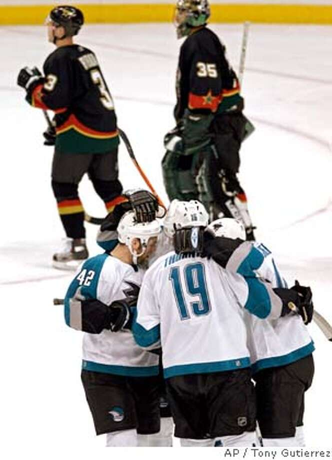 Dallas Stars' Stephane Robidas (3) and goalie Marty Turco (35) skate off the ice as San Jose Sharks Tom Preissing (42) and other teammates celebrate the overtime goal made by Joe Thornton (19) during NHL hockey action in Dallas, Monday, April 3, 2006. The Sharks defeated the Stars 3-2. (AP Photo/Tony Gutierrez) Photo: TONY GUTIERREZ
