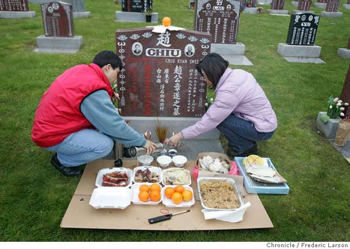 {object name} Fee Chu (left) of San Mateo the daughter and Helen Wong (grand daughter) prepare a small feast at the grave site of Chiu Kyan Swee who died 1999 at the age of 95. Ching Ming or