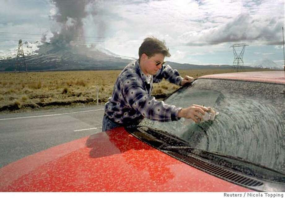AUC02:NEW ZEALAND-VOLCANO:MOUNT RUAPEHU,NEW ZEALAND,25SEP95- A motorist wipes ash from the windshield of his car as Mount Ruapehu behind erupts ash and rocks September 25. The country's largest volcano has been erupting for the past week covering the central North Island area with ash. NEW ZEALAND OUT rt/Photo by Nicola Topping/New Zealand Herald REUTERS Photo: NICOLA TOPPING