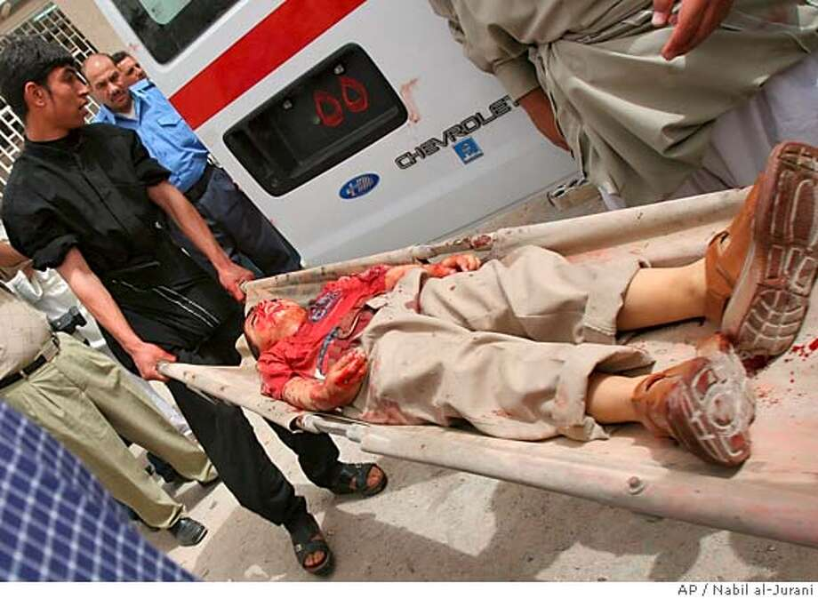 ** EDS NOTE GRAPHIC CONTENT ** An Iraqi man carries the body of a child who was shot in a drive-by shooting in a market Monday April 3, 2006 in Basra, Iraq. Drive-by shooters killed six people included a navy officer, two policemen, two workers at an electrical plant, and a boy, police said, as U.S. Secretary of State Condoleezza Rice and British Foreign Secretary Jack Straw urged Iraqi leaders to form a government as soon as possible to curb the bloodshed and rein in sectarian militias behind much of the country's violence.(AP Photo/Nabil al-Jurani) EDS NOTE GRAPHIC CONTENT Photo: NABIL AL-JURANI