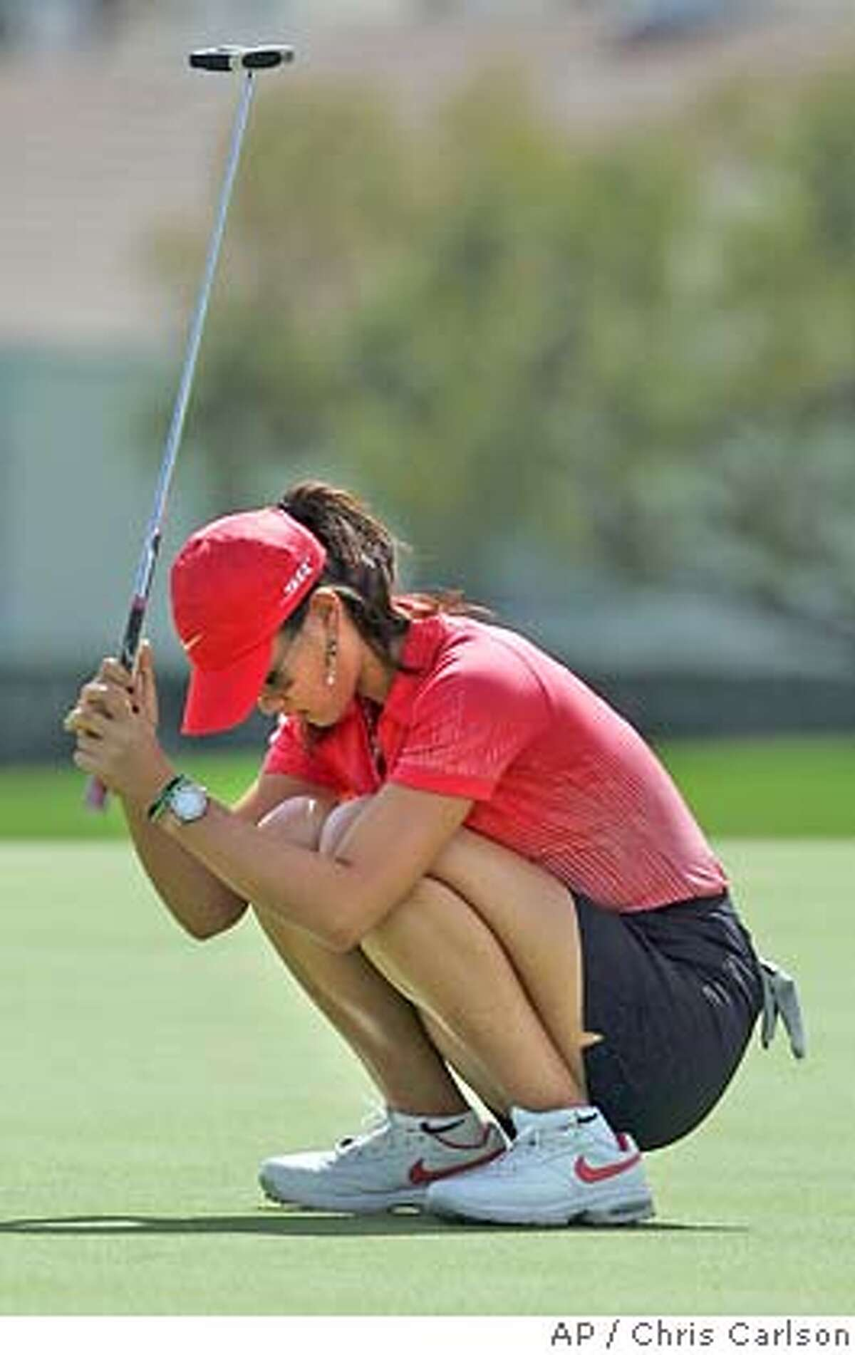 Michelle Wie, left, reacts after failing to make the playoff on the the 18th green during the final round of the Kraft Nabisco Championship golf tournament Sunday, April 2, 2006, at Mission Hills Country Club, in Rancho Mirage, Calif. (AP Photo/Chris Carlson)