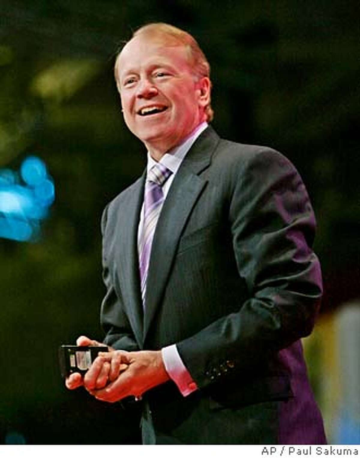 ** FILE ** Cisco Systems CEO John Chambers smiles during a keynote address at the Oracle Open World conference in San Francisco, in this Oct. 24, 2006, file photo. Chambers received compensation the company valued at $12.8 million in fiscal 2007, though his total pay package was actually much higher as he cashed out $50.9 million in stock options while the networking gear maker continues to profit mightily from a boom in demand for Internet bandwidth. (AP Photo/Paul Sakuma, file) OCT. 24, 2006 FILE PHOTO