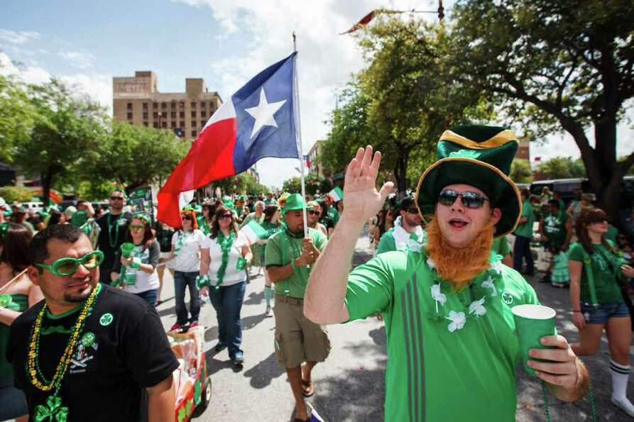 Brian Somner waves as he walks with members of the Sons of Ireland Houston during the 53rd Annual St