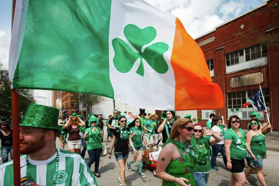 Jonathan Stephen carries an Irish flag as he walks with members of the Sons of Ireland Houston.