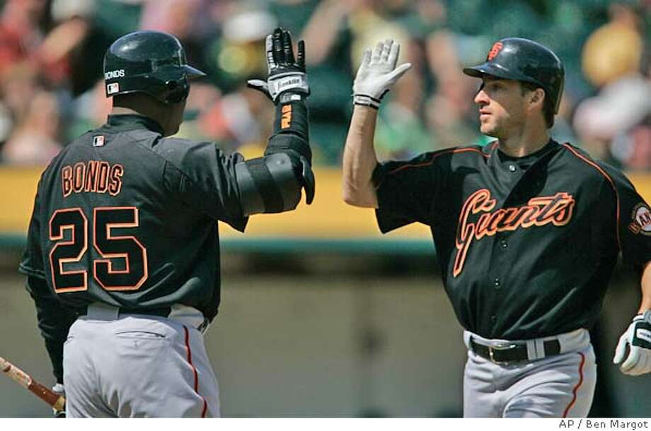 San Francisco Giants' Barry Bonds (25) congratulates Steve Finley, right, after Finley's solo home run hit off Oakland Athletics' Esteban Loaiza in the first inning of an exhibition baseball game Saturday, April 1, 2006, in Oakland, Calif. (AP Photo/Ben Margot) Photo: BEN MARGOT