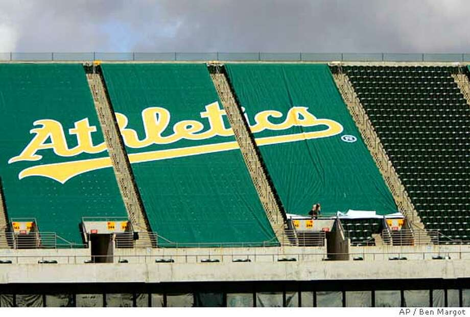 ** ADVANCE FOR WEEKEND EDITIONS, MARCH 18-19 ** Workers affix a green tarp over upper deck seats at McAfee Coliseum Wednesday, March 15, 2006, in Oakland, Calif. By the time the Oakland Athletics open their season against the New York Yankees next month, the team will have strung a tarpaulin over 10,000 of the most unattractive upper-deck seats, reducing McAfee Coliseum to one of the smallest in pro baseball. Counterintuitive as it may sound, the A's, who have struggled with low attendance, hope the removal of the stadium's entire third deck will boost season ticket sales and generate renewed fan loyalty. (AP Photo/Ben Margot) Photo: BEN MARGOT
