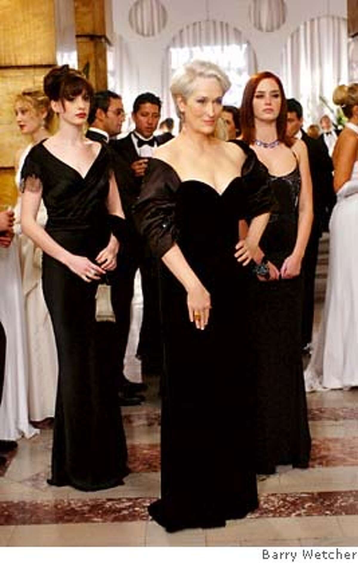 At an important party, fashion magazine editor Miranda Priestly (Meryl Streep) is flanked by her two assistants, Andy (Anne Hathaway, left) and Emily (Emily Blunt). PHOTOGRAPHS TO BE USED SOLELY FOR ADVERTISING, PROMOTION, PUBLICITY OR REVIEWS OF THIS SPECIFIC MOTION PICTURE AND TO REMAIN THE PROPERTY OF THE STUDIO. NOT FOR SALE OR REDISTRIBUTION. Ran on: 06-30-2006 Andy Sachs (Anne Hathaway) gets a rude awakening in The Devil Wears Prada, a dark look inside New Yorks fashion industry.