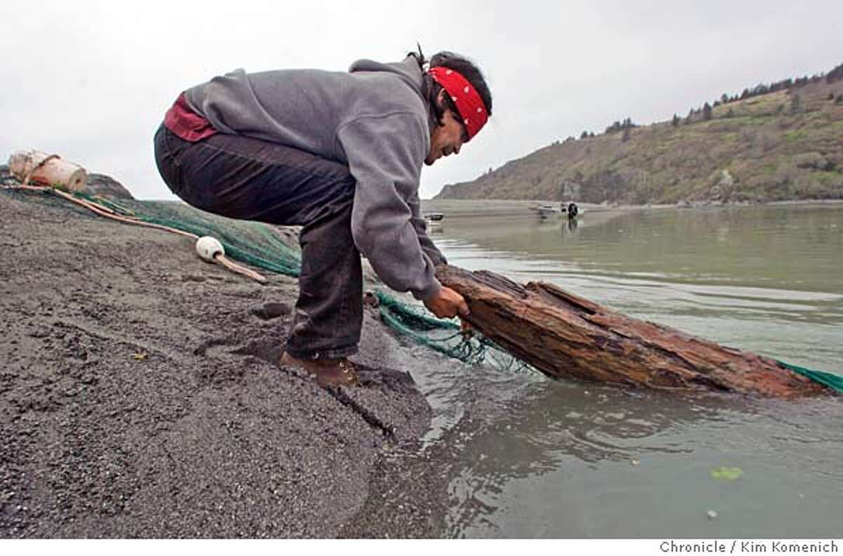 KLAMATH02_362_KK.JPG EDS: This photo is probably the most symbolic photo I have of the lack of fish and the changing nature of the Kalamth fishery.--kk) Yurok tribe member Dennis Scott removes a log from his eel net at the mouth of the Klamath River. (The Yurok fishermen we met jokingly call the logs in their nets