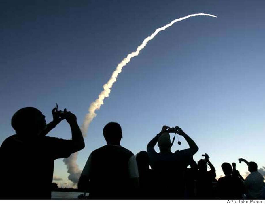 Spectators at Jetty Park pier watch as a Delta II rocket with the Dawn spacecraft aboard, lifts off from the Cape Canaveral Air Force Station in Cape Canaveral, Fla., Thursday, Sept. 27, 2007. NASA's Dawn spacecraft rocketed away toward an unprecedented double encounter in the asteroid belt between Mars and Jupiter. (AP Photo/John Raoux) Photo: John Raoux