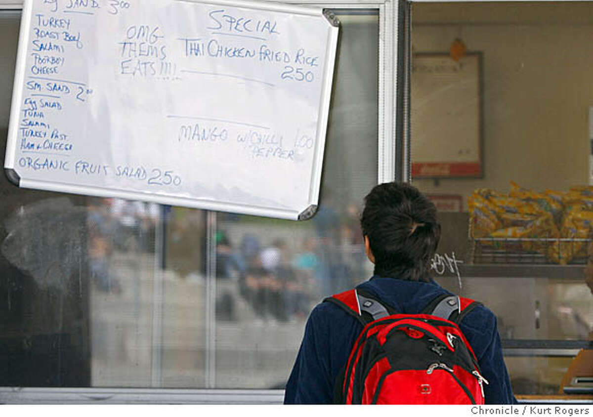 A student looks over the menu at Albany High. Lunch at Albany High School and the food that the kids are eating. The law says the schools can' t serve junk food but some foods just meets the state requirements. _R1_0088.JPG ALBANY, CA, on Friday, September, 21. photo taken: 9/21/07 KURT ROGERS / The Chronicle *
