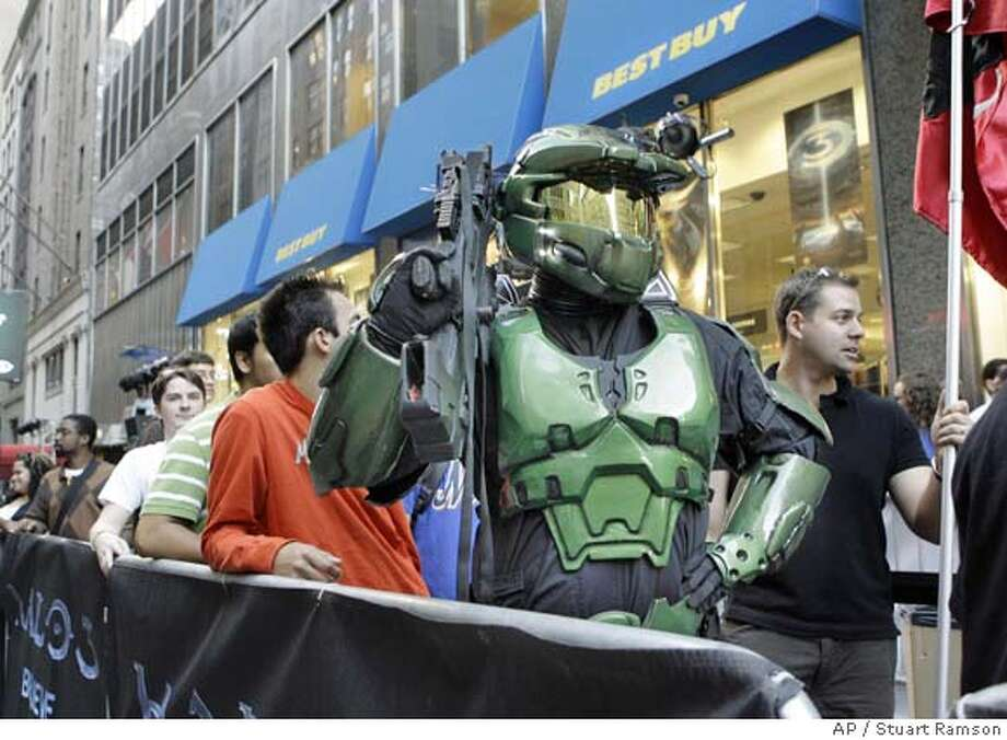 In this photo released by Xbox, Jim Cush, of Babylon, N.Y., dressed as Master Chief, the hero of the video game Halo 3, waits in line with other fans to be among the first the purchase the game outside Best Buy in Manhattan, Monday, Sept 24, 2007. Microsoft's Halo 3, the most anticipated video game in history, has pre-sold more than 1.5 million copies and officially goes on sale at midnight tonight.( AP Photo/Xbox/Stuart Ramson) Photo: Stuart Ramson