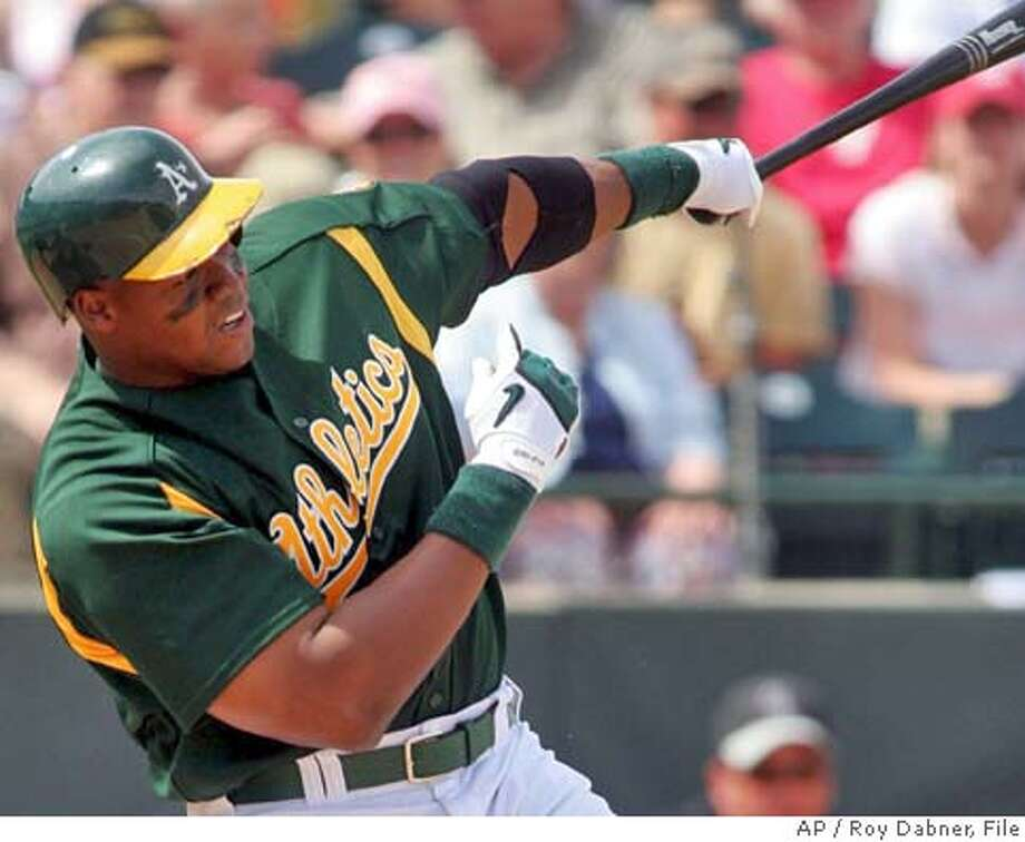Oakland Athletics' Frank Thomas follows through on his fifth-inning, solo home run off Colorado Rockies' Josh Fogg, Sunday, March 26, 2006, in Phoenix.(AP Photo/Roy Dabner) Photo: ROY DABNER