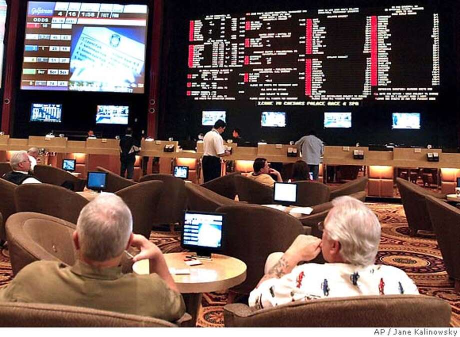 Patrons watch television as they wait in the Caesars Palace sports book for the 2006 Men's College Basketball Tournament bidding sheets in Las Vegas, NV on Monday, March 13, 2006. Patrons will be able to start making bets on March Madness at 7:00 A.M., Thursday, March 17, 2006. (AP Photo/Jane Kalinowsky) Photo: JANE KALINOWSKY
