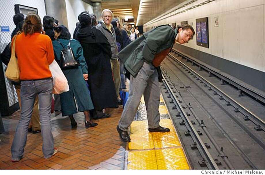 BART_036_MJM.jpg  In a bit of wishful thinking, Darren M. Kelly, a SF architect who lives in Lafayette leans out over the tracks at the Powell Street BART Station looking for an eastbound train despite the announcement by the BART PA system that said it would be over an hour before BART resumes service. BART experienced a 90-minute shutdown caused by a computer networking problem during the height of the evening commute Wednesday. BART stopped regular service after the problem hit at 5:27 p.m., moving all trains under manual control to the nearest station. System officials said trains had resumed about 6:50 p.m. BART spokesman Linton Johnson said the problem was different from the software glitch that plagued the system Tuesday, but had the same effect -- a service shutdown.  Photo by Michael Maloney / San Francisco Chronicle on 3/29/06 in San Francisco,CA MANDATORY CREDIT FOR PHOTOG AND SF CHRONICLE/ -MAGS OUT Photo: Michael Maloney