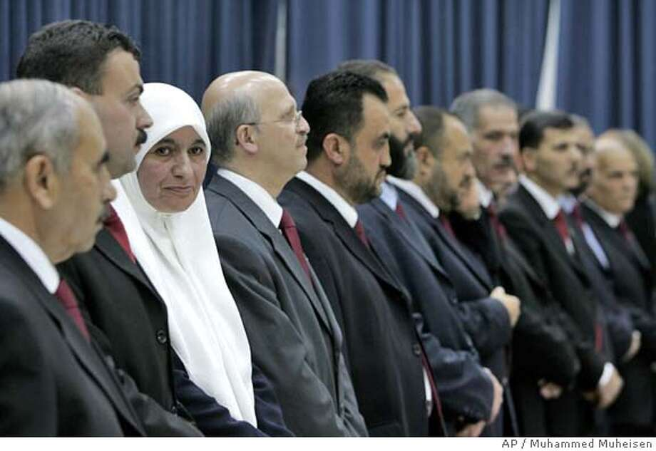 Dr. Mariam Saleh, third left, the only woman member of the new Palestinian government, pauses among other members of the cabinet, during the swearing in ceremony at the headquarters of Palestinian Authority President Mahmoud Abbas in the West Bank city of Ramallah, Wednesday March 29, 2006. Hamas formally took power Wednesday, with the Palestinian president swearing in its 24-member Cabinet, including 14 ministers who served time in Israeli prisons. (AP Photo/Muhammed Muheisen) Photo: MUHAMMED MUHEISEN