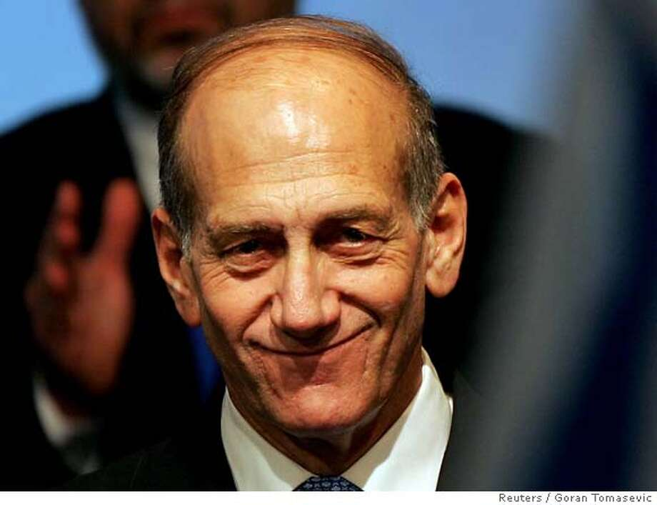 Israeli interim Prime Minister Ehud Olmert smiles after early exit polls in Israel Photo: GORAN TOMASEVIC