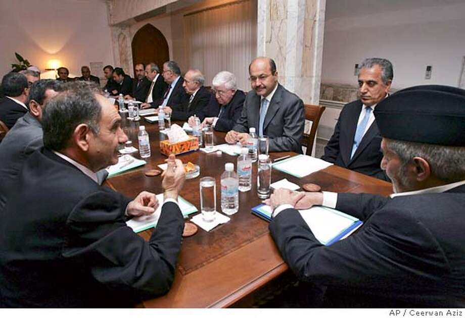 Iraqi Sunni politician Saleh al-Mutlak , left, speaks to colleagues during an Iraqi government cabinet meeting attended by US ambassador Zalmay Khalilzad, second from right, in Baghdad Tuesday March 28, 2006. Multiparty negotiations on forming a new government resumed Tuesday after Shiite politicians halted the talks in response to a U.S.-Iraqi raid on Sunday that Shiite officials said took place in a mosque.(AP Photo/ Ceerwan Aziz, Pool) POOL PHOTO Photo: CEERWAN AZIZ