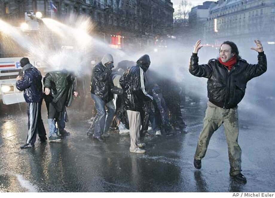 Police use their water canon on youths during a protest against the first job contract law, known as CPE, Tuesday, March 28, 2006 in Paris. Tens of thousands of protesters poured onto France's streets and striking workers hobbled transport services Tuesday, increasing pressure on embattled Prime Minister Dominique de Villepin to withdraw a contested new jobs contract for youths. (AP Photo/Michel Euler) Photo: MICHEL EULER