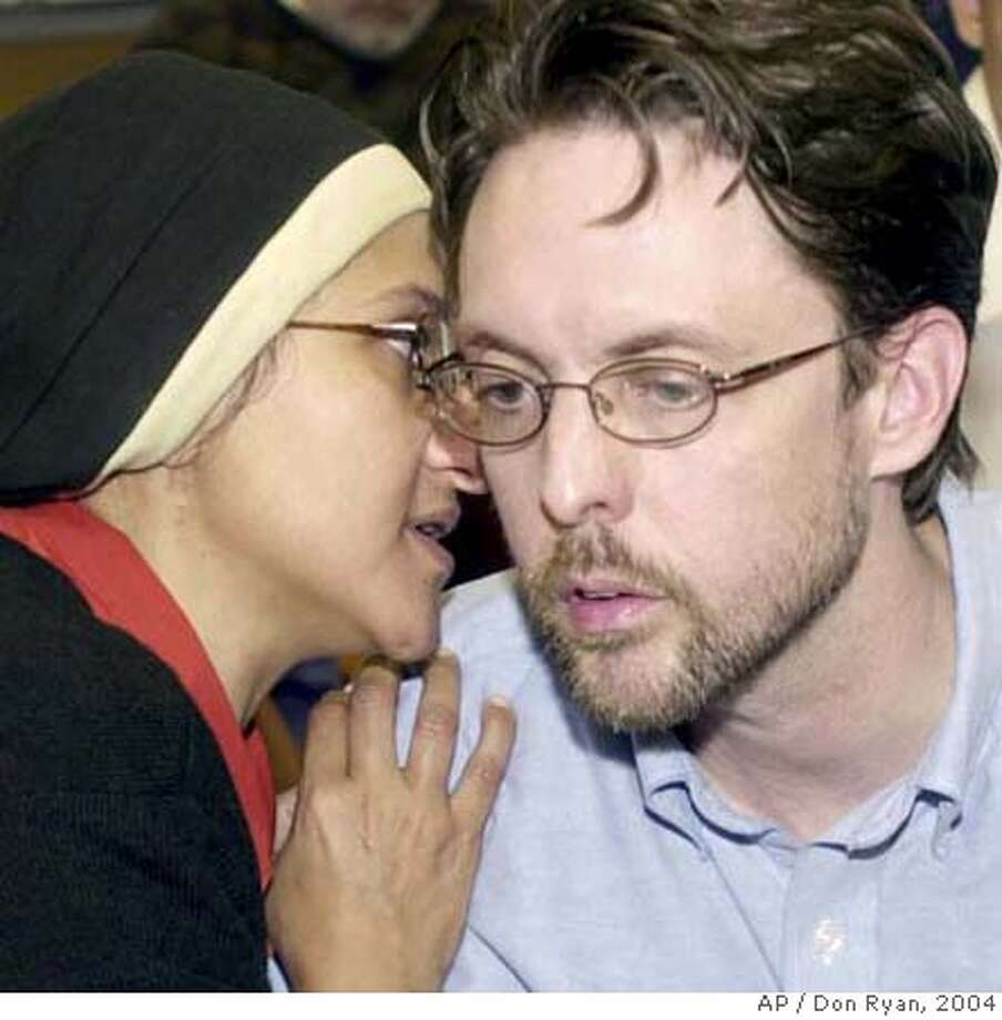 "** FILE ** Portland attorney Brandon Mayfield, right, confers with his wife, Mona Mayfield, during an announcement in Portland, Ore., in this May 24, 2004, file photo, that a federal judge dismissed the case against Mayfield in which he had been arrested in the Madrid train bombings investigation. U.S. District Judge Ann Aiken ruled in Eugene, Ore., Wednesday, Sept. 26, 2007, that the Foreign Intelligence Surveillance Act, as amended by the Patriot Act, ""now permits the executive branch of government to conduct surveillance and searches of American citizens without satisfying the probable cause requirement of the Fourth Amendment."" Mayfield had sued the federal government after he was mistakenly linked to the 2004 Madrid train bombings. (AP Photo/Don Ryan) Photo: Don Ryan"