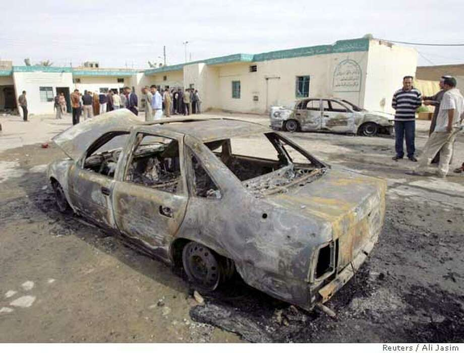 Burnt car sits outside mosque following violence between US troops and Iraqis in Baghdad Photo: ALI JASIM