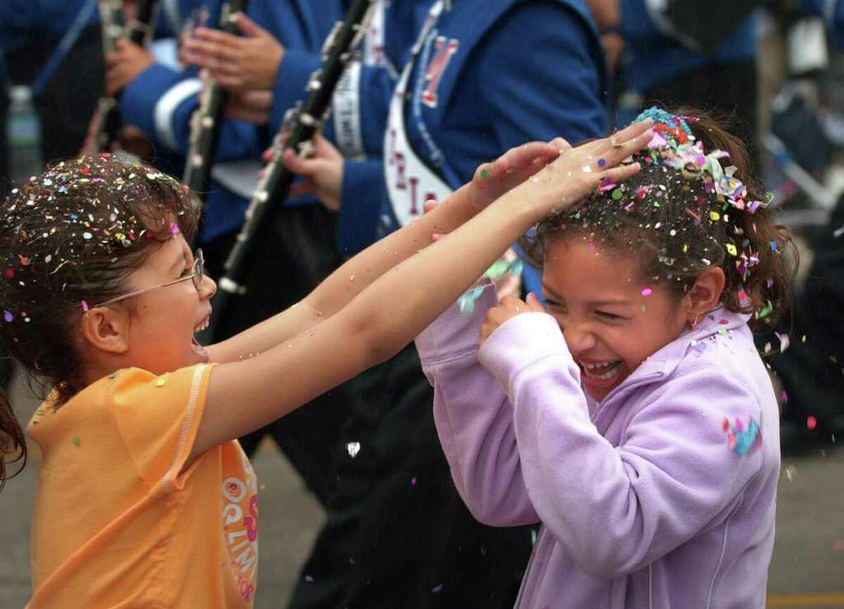 Metro daily - Ember Ayala, left, hits Arianh Campos with Fiesta cascarones during The Battle of Flowers Parade along Broadway, Friday, April 23, 2004. photo Bob Owen