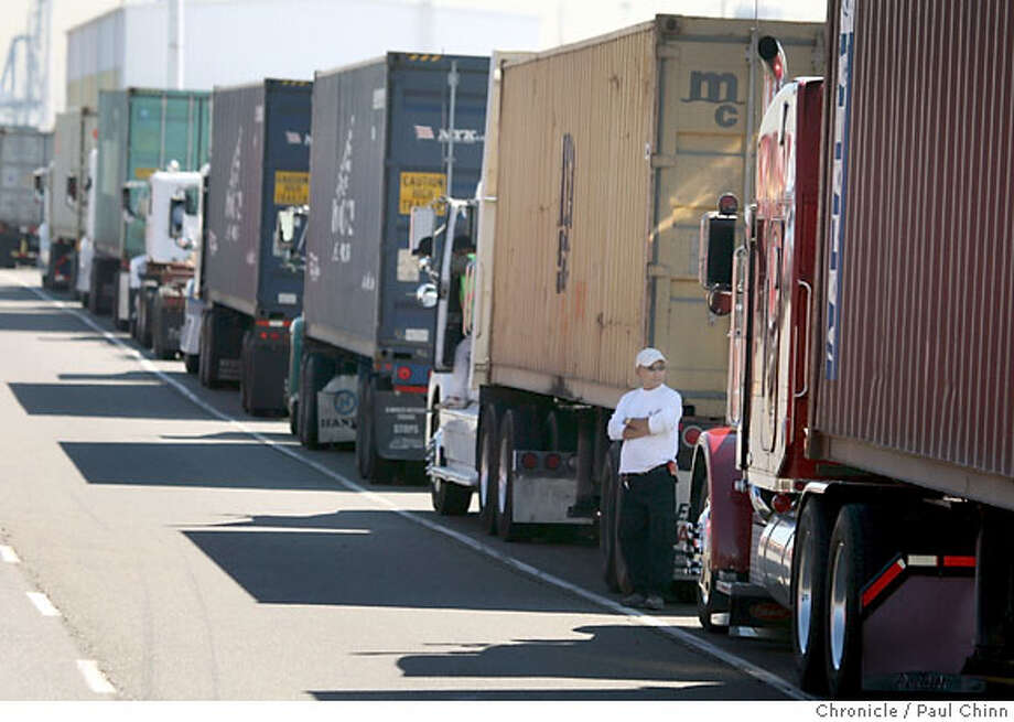 A truck driver stands outside of his rig while he waited in a long line of trucks for the port to reopen after the lunch break at the Port of Oakland in Oakland, Calif. on Wednesday, Sept. 26, 2007. The Coalition for Clean and Safe Ports says dirty emissions from unsafe trucks are leading to a higher than normal level of unsafe air and is contributing to a high rate of health issues in West Oakland neighborhoods. PAUL CHINN/The Chronicle Photo: PAUL CHINN