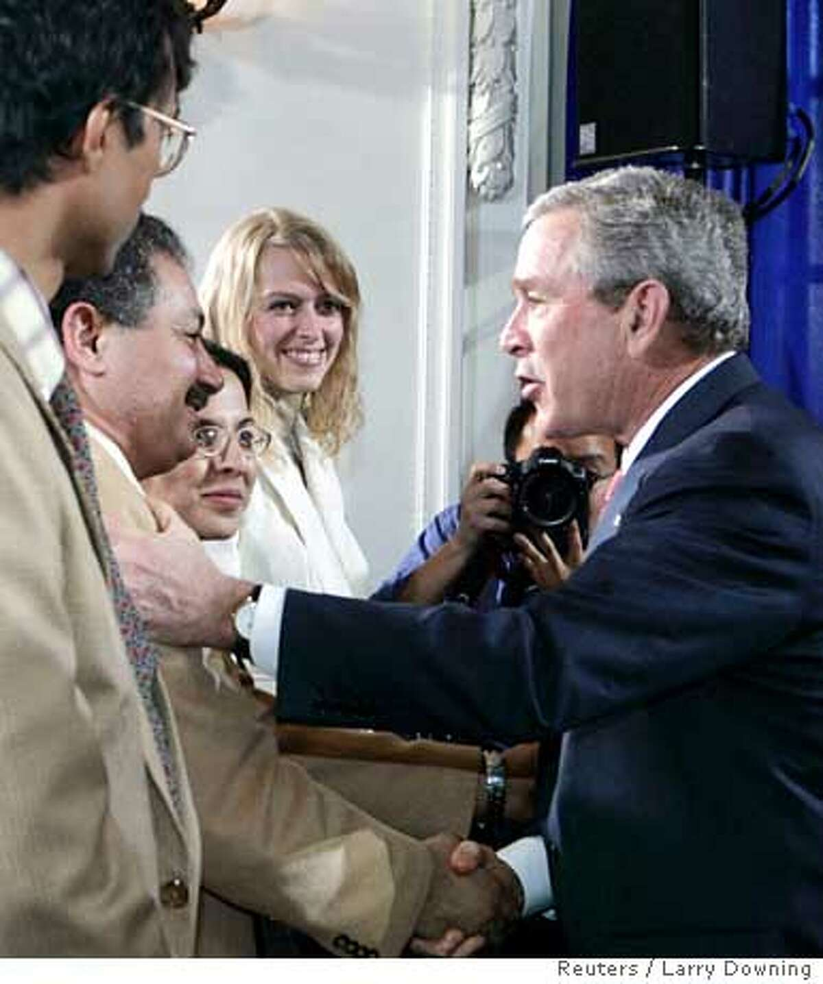 U.S. President George W. Bush (R) greets newly sworn-in U.S. citizens at the swearing-in ceremony of immigrants as U.S. citizens during a U.S. Naturalization Ceremony at the Daughters of the American Revolution Administration Building in Washington March 27, 2006. REUTERS/Larry Downing