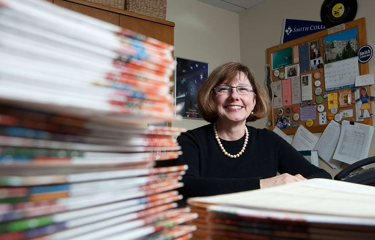 In this March 1, 2012 photo provided by Smith College, Debra Shaver, dean of admission, sits next to stacks of applications to the Smith College Class of 2016 from prospective students in Northhampton, Mass. Smith is among just a few colleges that invite parents to submit letters on behalf of their children (either as part of the application itself, or in a follow-up invitation after the application is received).