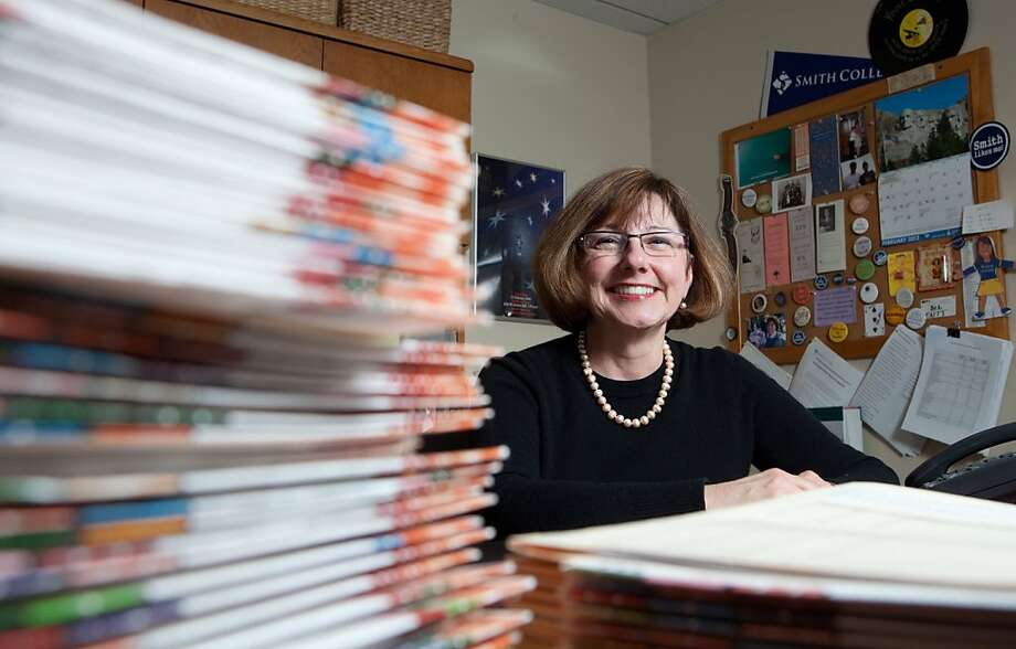 "In this March 1, 2012 photo provided by Smith College, Debra Shaver, dean of admission, sits next to stacks of applications to the Smith College Class of 2016 from prospective students in Northhampton, Mass. Smith is among just a few colleges that invite parents to submit letters on behalf of their children (either as part of the application itself, or in a follow-up invitation after the application is received). ""You might think they do nothing but brag,"" Shaver said. ""But parents really nail their kids. They really get to the essence of what their daughter is about in a way we can't get anywhere else."" (AP Photo/Smith College, Samuel A. Masinter) Photo: Samuel A. Masinter, Associated Press"