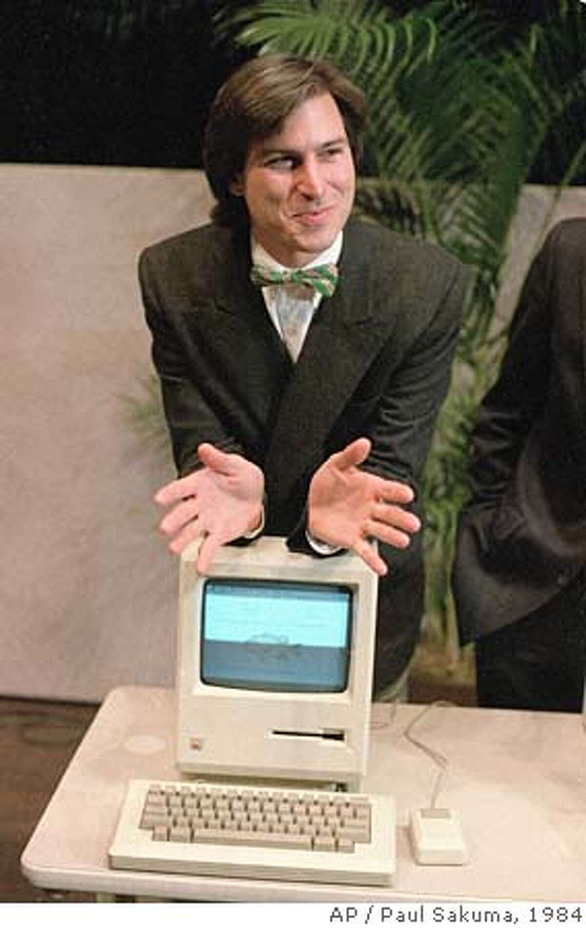 """** ADVANCE FOR SUNDAY MARCH 26 **FILE**Steven Jobs, chairman of the board of Apple Computer, leans on the new """"Macintosh"""" personal comptuer following a shareholder's meeting Jan. 24, 1984 in Cupertino, Ca. The Macintosh, priced at $2,495, is challenfing IBM in the personal computer market. As the storied company celebrates its 30th birthday in a week, Apple Computer Inc. will be showing its age: It will have brushed off its bruises from product failures and arguably misguided decisions to emerge with a shine that's more than skin-deep. Its luster now is brighter than ever, but for all of its recent successes, Apple also has its share of challenges ahead as it matures into a digital media provider. (AP Photo/Paul Sakuma)"""
