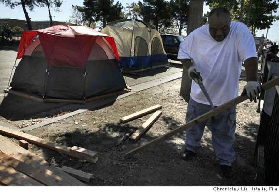 TENT26_024.JPG John John Foster, 38 years old, cutting wood to help make stronger foundations for the tents. Outraged Richmond residents are setting up another tent city to protest homicides, similar to tent cities from last year, at Nevin Park near the fatal officer-involved shooting on Monday night.  Liz Hafalia/The Chronicle/Richmond/9/26/07  **John John Foster cq �2007, San Francisco Chronicle/ Liz Hafalia  MANDATORY CREDIT FOR PHOTOG AND SAN FRANCISCO CHRONICLE. NO SALES- MAGS OUT. Photo: Liz Hafalia