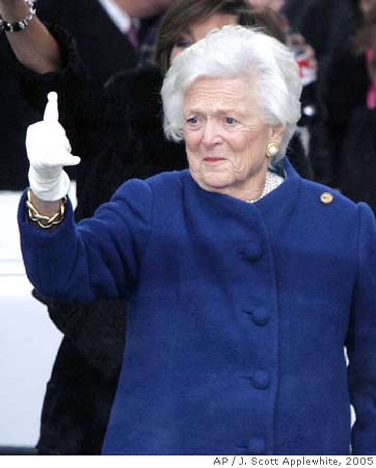 """Former first lady Barbara Bush gives the """"Hook 'em Horns"""" symbol from the reviewing stand during President Bush's Inaugural Parade Thursday, Jan. 20, 2005, in Washington. (AP Photo/J. Scott Applewhite) Ran on: 01-22-2005 Photo: J. SCOTT APPLEWHITE"""