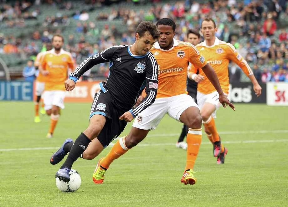 SAN FRANCISCO, CA - MARCH 17:  Chris Wondolowski #8 of the San Jose Earthquakes tries to dribble around Jermaine Taylor #4 of the Houston Dynamo at AT&T Park on March 17, 2012 in San Francisco, California. Photo: Ezra Shaw, Getty Images / 2012 Getty Images