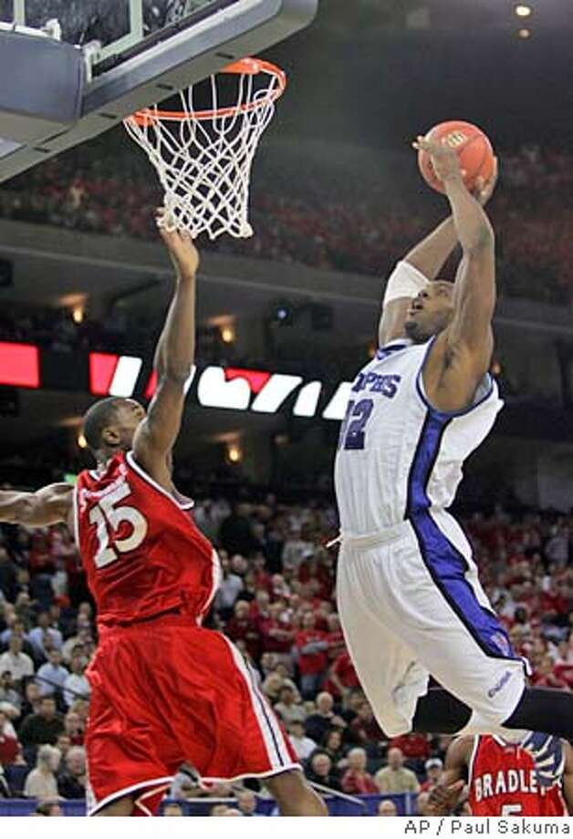 Memphis' Joey Dorsey, right, goes up for a basket against Bradley's Marcellus Sommerville during the second half of their NCAA Tournament regional semifinal college basketball game, Thursday, March 23, 2006, in Oakland, Calif. (AP Photo/Paul Sakuma) Photo: PAUL SAKUMA