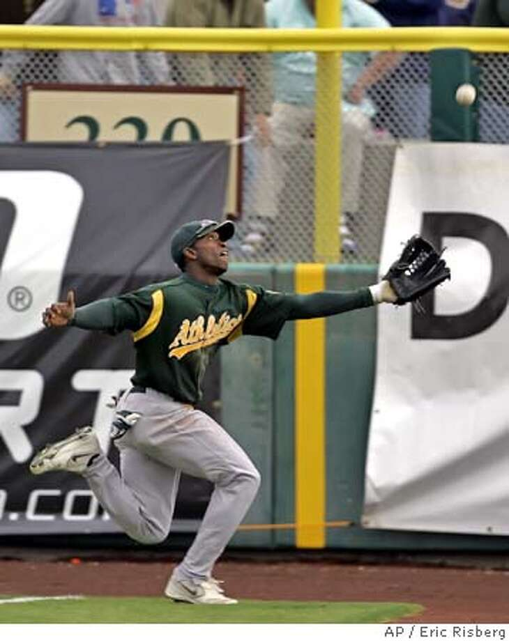 Oakland Athletics' right fielder Freddie Bynum runs to catch a fly foul ball hit by the San Francisco Giants' Mike Matheny during the fifth inning of their spring training game in Scottsdale, Ariz., Tuesday March 21, 2006.(AP Photo/Eric Risberg) Photo: ERIC RISBERG