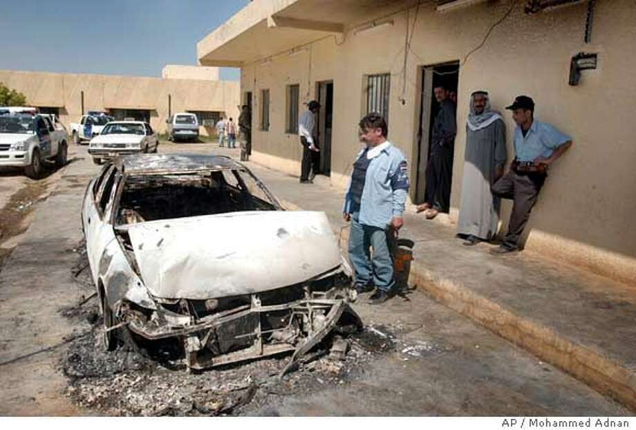 Iraqi policemen look at their damaged vehicle at a police station, in Muqdadiyah, 90 kilometers (60 miles) north of Baghdad, Iraq, Tuesday, March 21, 2006. Insurgents stormed a jail at dawn Tuesday in the Sunni Muslim heartland north of Baghdad, killing at least 15 police officers and a courthouse guard. (AP Photo/Mohammed Adnan) Photo: MOHAMMAD ADNAN