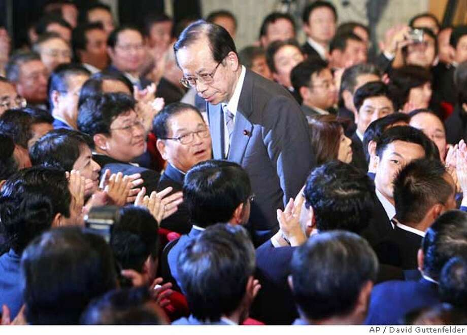 Former Chief Cabinet Secretary Yasuo Fukuda, center, bows to lawmakers after being elected president of the ruling Liberal Democratic Party, Sunday, Sept. 23, 2007, in Tokyo. Moderate veteran Fukuda easily won election as president of Japan's struggling ruling party Sunday, assuring his selection as the new prime minister in a parliamentary vote later this week. (AP Photo/David Guttenfelder) Photo: David Guttenfelder