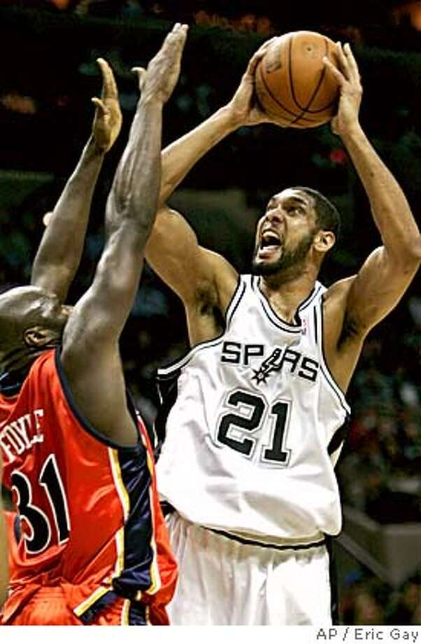 San Antonio Spurs forward Tim Duncan, right, shoots over Golden State Warriors defender Adonal Foyle during the first quarter in NBA basketball action in San Antonio, Tuesday, March 21, 2006. (AP Photo/Eric Gay) Photo: ERIC GAY