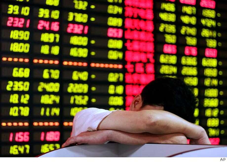** FILE ** An investor takes a nap in front of the stock price screen at a securities company in Shanghai, China, in this July 4, 2007, file photo. Chinese stocks fell Tuesday September 11, 2007, with the key Shanghai Composite Index tumbling 4.5 percent following reports that inflation surged in August to an 11-year high. The Shanghai index, which measures both local currency and foreign-denominated shares, closed at 5,113.97, down 241.32 points. (AP Photo) Photo: Ap