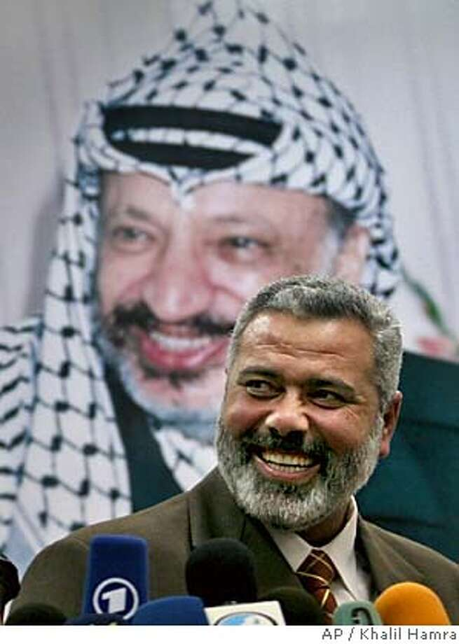 Palestinian incoming Prime Minister Ismail Haniyeh, from the Islamic group Hamas, smiles as he speaks to journalists after meeting Palestinian Authority President Mahmoud Abbas in Gaza City Sunday March 19, 2006. Haniyeh met Abbas to present his new Cabinet and said after the meeting, his Cabinet would have 24 members, 10 from Gaza and 14 from the West Bank. Fellow Hamas leader Mahmoud Zahar will be the new foreign minister, he said. Abbas said he would submit the list to the PLO executive committee and then to the parliament if it approves. In the background a portrait of the late Yasser Arafat.(AP Photo/Khalil Hamra) Photo: KHALIL HAMRA