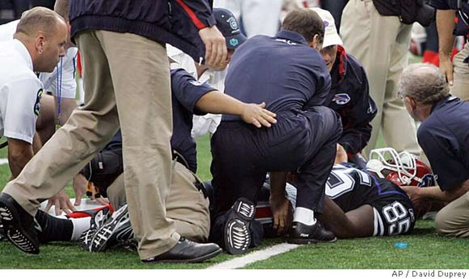Buffalo Bills reserve tight end Kevin Everett is helped by trainers after an injury during the second half of the NFL football game against the Denver Broncos at Ralph Wilson Stadium in Orchard Park, N.Y., Sunday, Sept. 9, 2007. Everett had surgery Sunday after injuring his spine on a kickoff and there is concern about whether he will be able to walk again. (AP Photo/David Duprey) Photo: David Duprey