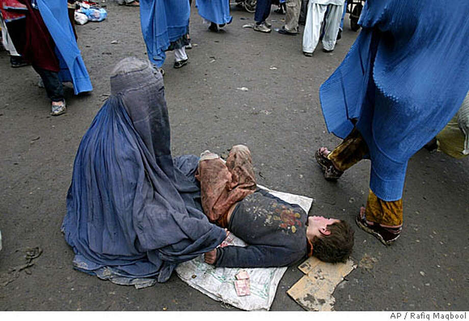 An Afghan woman with her son begs for alms outside a mosque in Kabul, Afghanistan, Friday, Feb. 24, 2006. Despite some economic and social progress since the fall of the Taliban, Afghan culture makes it difficult for women to work outside the home and many women are forced to beg to survive. (AP Photo/Rafiq Maqbool) STAND ALONE Photo: RAFIQ MAQBOOL