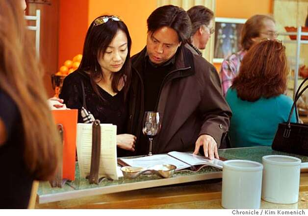 "NAPA19_072_KK.JPG  Sheryl Lai and Hau Hsu of Los Angeles look over the wine descriptions at Darioush Winery.  Many Napa Valley wineries are charging a top dollar for a tasting. Many now require reservations. Rubicon Winery charges $25 for a ""passport"" for each customer, which includes valet parking and a tasting. Darioush Winery charges $15 for a tasting. With the opening of these Vegas-like wine palaces, Napa is now a high end tourist destination--a sort of Hamptons of the West for foodies.  San Francisco Chronicle photo by Kim Komenich  3/11/06Ran on: 03-19-2006  Sheryl Lai and Hau Hsu look over Darioush Winery's selections.Ran on: 03-19-2006  Sheryl Lai and Hau Hsu look over Darioush Winery's selections.Ran on: 03-19-2006 Photo: Kim Komenich"