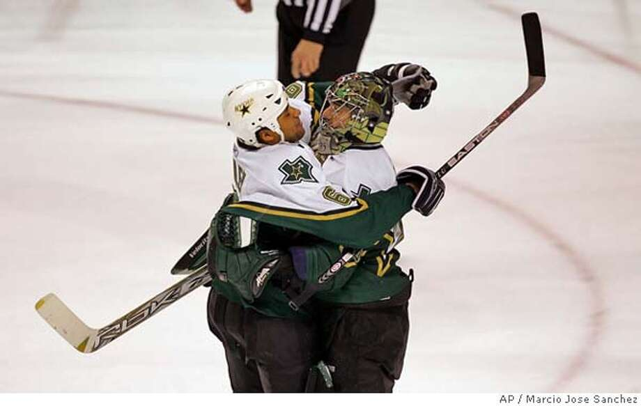 Dallas Stars goalie Marty Turco, right, is hugged by teammate Trevor Daley after the Stars' 4-3 penalty shootout win over the San Jose Sharks in an NHL hockey game in San Jose, Calif., on Saturday, March 18, 2006. (AP Photo/Marcio Jose Sanchez) EFE OUT Photo: MARCIO JOSE SANCHEZ